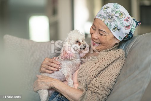 A woman with cancer is sitting on her couch at home. She is relaxed and happy. The woman's pet dog is sitting on her lap. She is smiling while embracing the dog. The woman is wearing a bandana to hide her hair loss from chemotherapy treatment