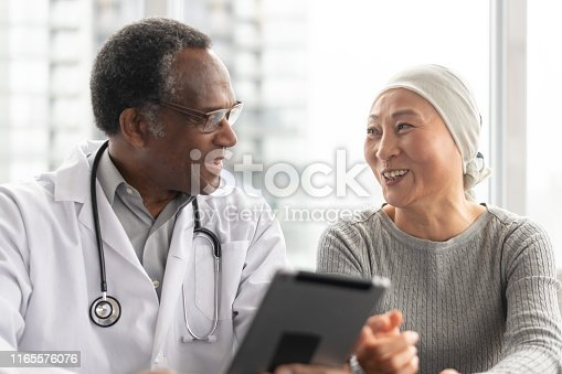 istock Woman with cancer reviews test results with doctor 1165576076