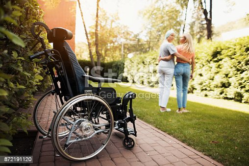 istock A woman with cancer stands up with her daughter. They embrace. Nearby is a wheelchair woman. 872191120