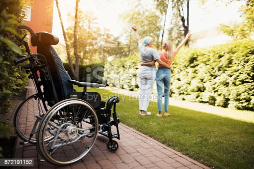 istock A woman with cancer stands up with her daughter. They embrace. Nearby is a wheelchair woman. 872191152