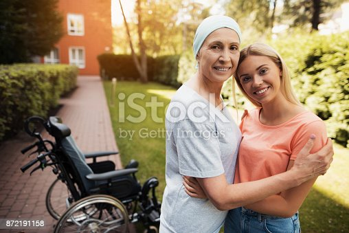 istock A woman with cancer stands up with her daughter. They embrace. Nearby is a wheelchair woman. 872191158