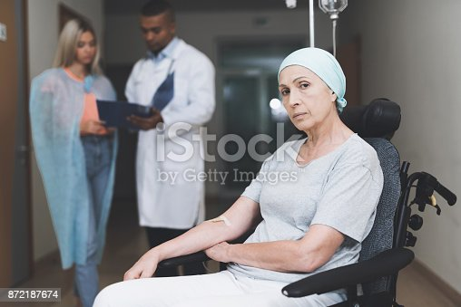 istock A woman with cancer, with a doomed look, is sitting in a wheelchair. Behind her daughter stands and talks to the doctor. 872187674