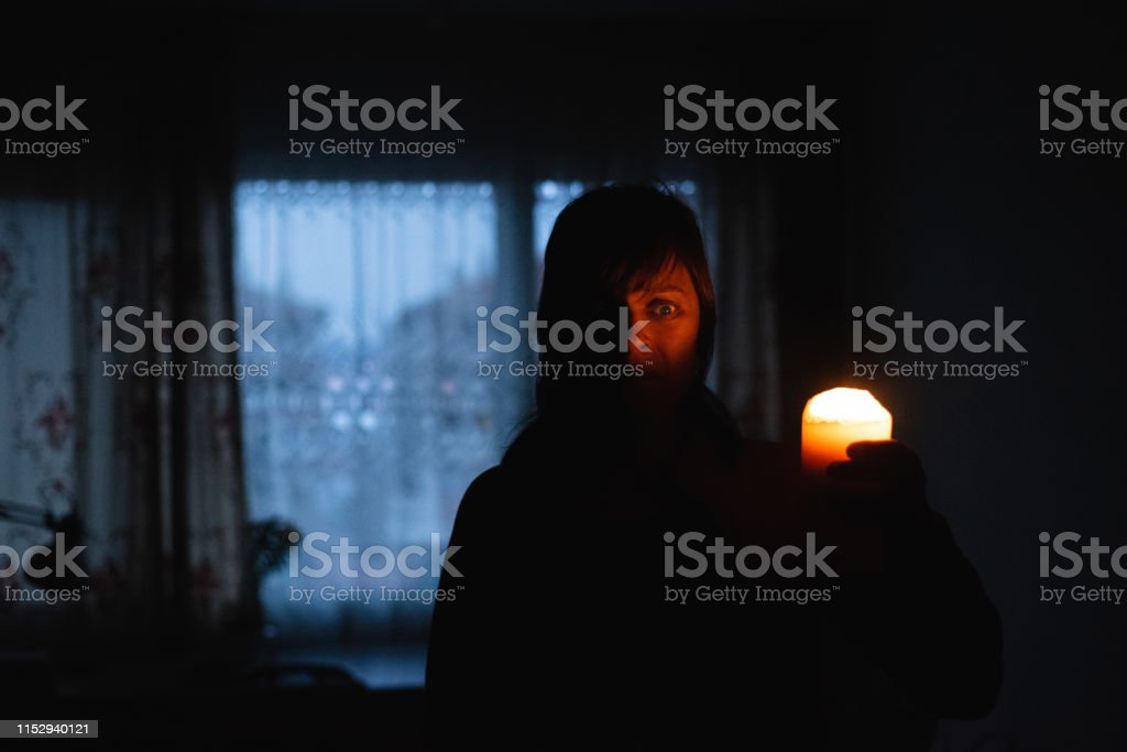 Woman with candle at home because of power cut Woman with candle at home because of power cut Adult Stock Photo