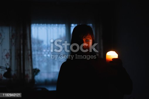istock Woman with candle at home because of power cut 1152940121