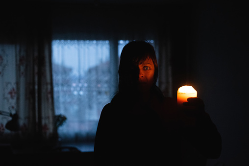 Woman With Candle At Home Because Of Power Cut Stock Photo - Download Image Now