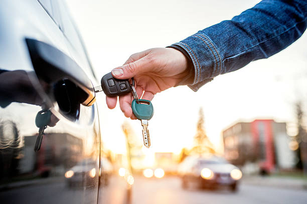 Woman with car key Unrecognizable woman opening her car with a key car key stock pictures, royalty-free photos & images