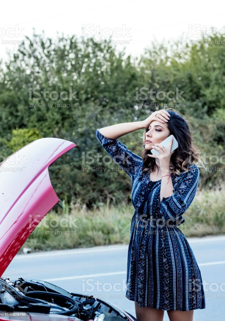 Attractive Young Woman in Dress with Lifted Vehicle Hood Calling...