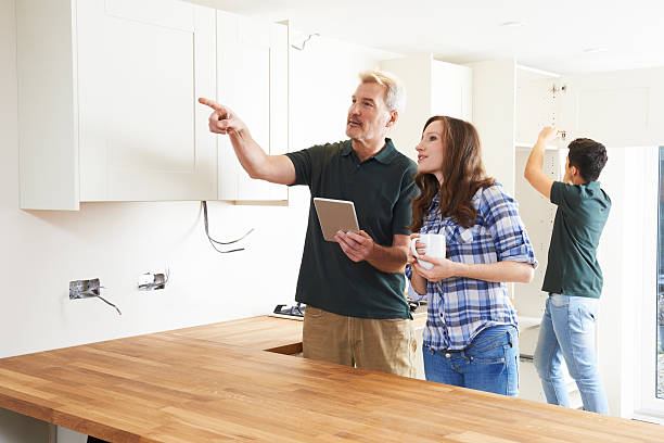 woman with carpenter looking at plans for kitchen - quality control stock photos and pictures