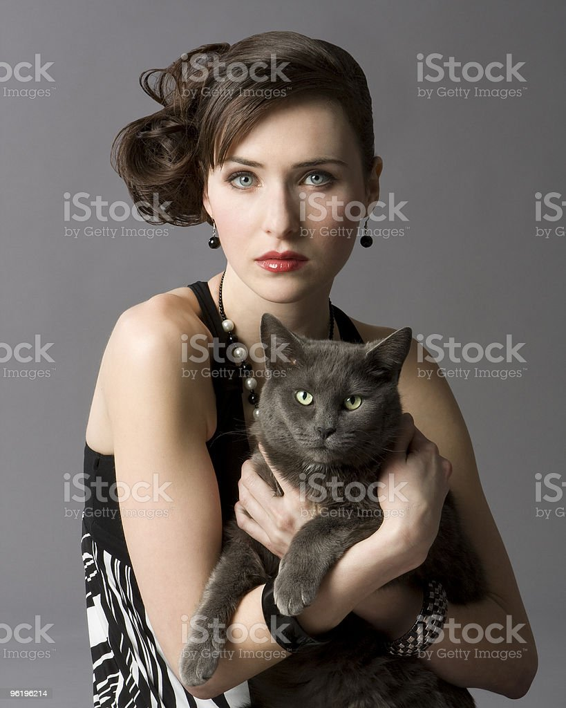 studio photo of elegant young woman holding gray cat.