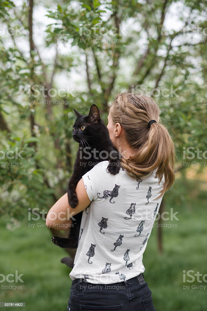 Young woman wearing cats print t-shirt holding her black cat in her...