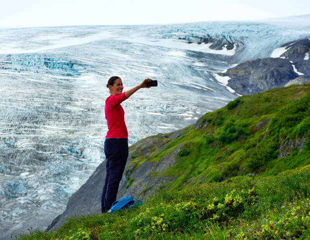 Woman with cell phone on hands taking a selfie. Exit Glacier in the background with its blue ice and white snow. Portrait, fine art. In Kenai Fjords National Park, Alaska. July 27, 2018 stock photo