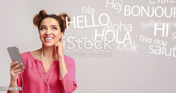istock Woman with cellphone hearing different languages on grey 1178902676