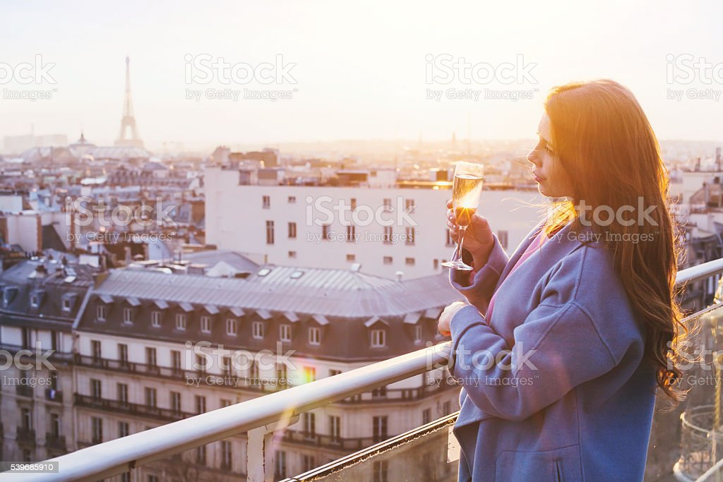woman with champagne in rooftop luxury restaurant in Paris stock photo