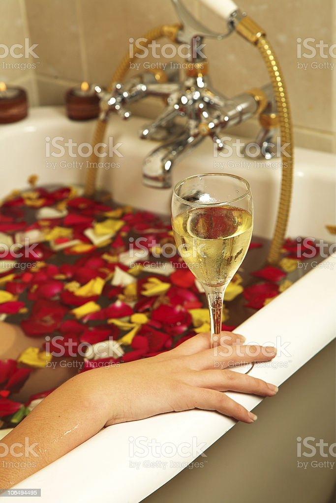woman with Champaign and rose petals royalty-free stock photo