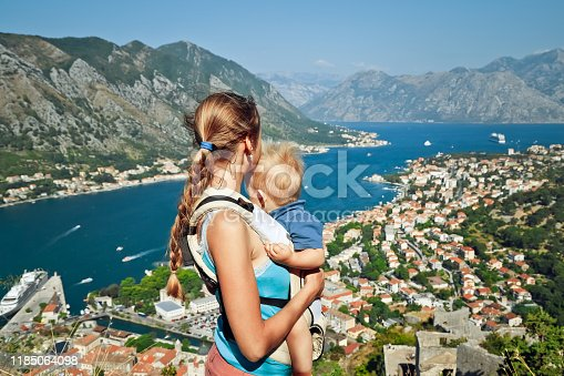 Woman with child in hands looks at the beautiful view of the Bay of Kotor from the top of mountain in Montenegro. The view from the back.
