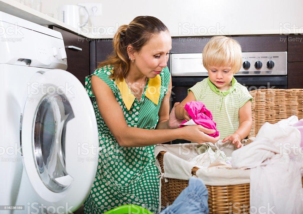 Woman with child near washing machine stock photo