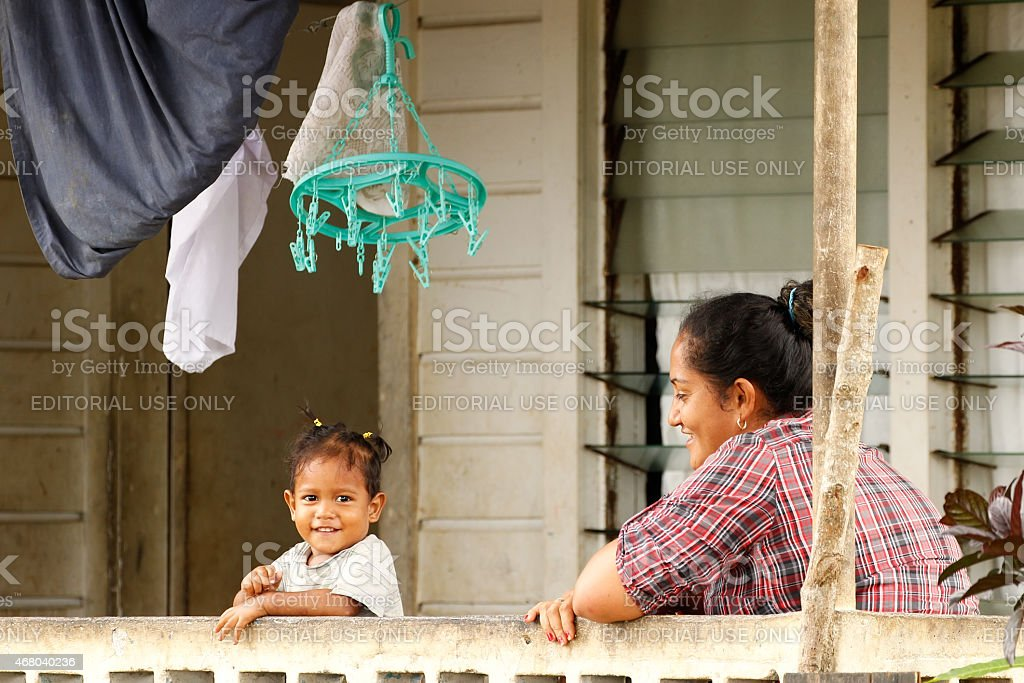 Woman with child sitting on a front porch of house stock photo