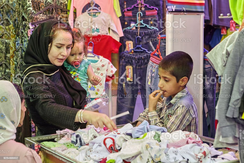 cfd8fe110b12 Woman With Children Chooses Clothes In Eastern Market Kashan Iran ...