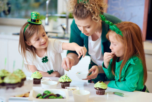woman with children decorating cupcakes - st patricks day stock photos and pictures