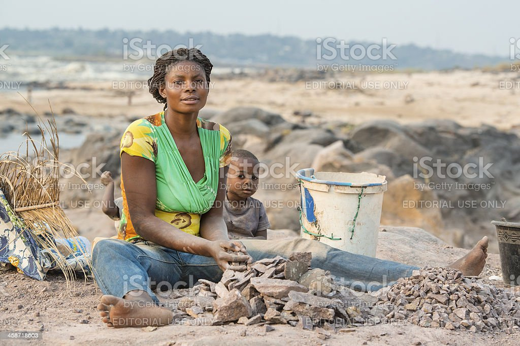 Woman with children is crushing stones for a living stock photo