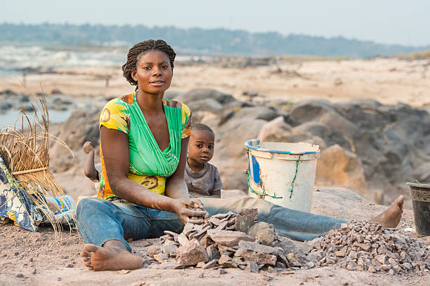 woman with children is crushing stones for a living - democratic republic of the congo stock photos and pictures