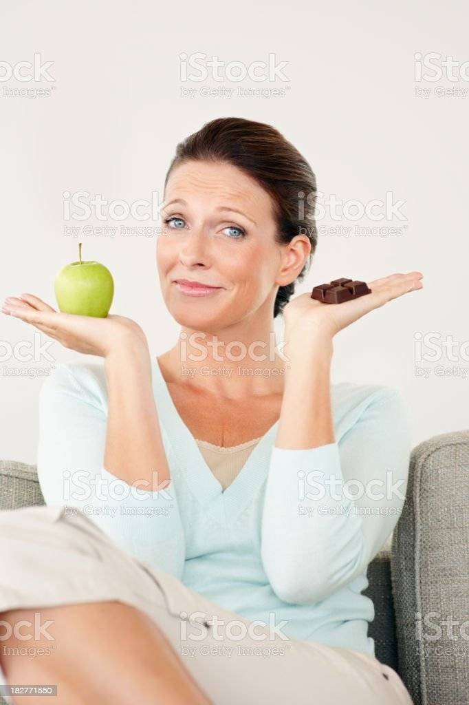 Woman with chocolate and apple choosing what to eat royalty-free stock photo