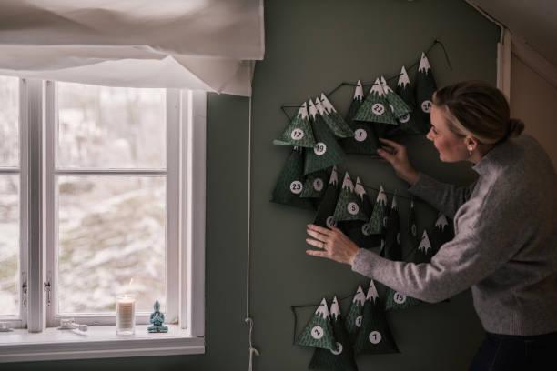 femme avec calendrier de noël avec des cadeaux - calendrier de l'avent photos et images de collection