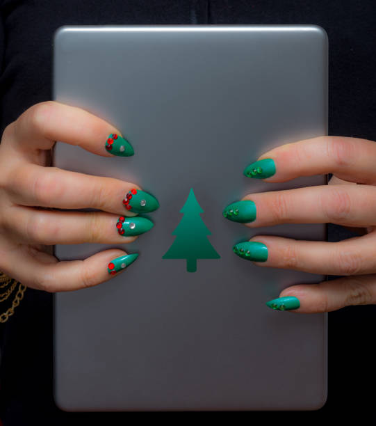 frau mit weihnachten maniküre hält einen weihnachts-tablet - nageldesign weihnachten stock-fotos und bilder