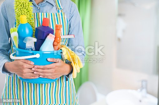 istock woman with cleaning equipment ready to clean house on bathroom background 943681194