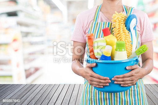 istock woman with cleaning equipment ready to clean house on empty of wooden table and office blur background 859357640