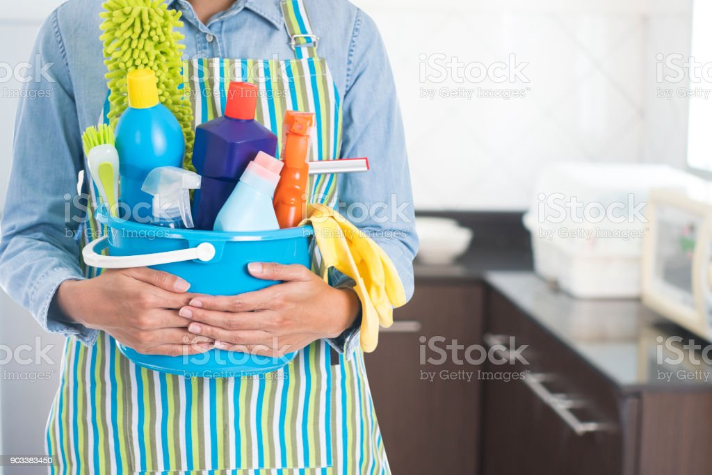 woman with cleaning equipment ready to clean house on kitchen background stock photo