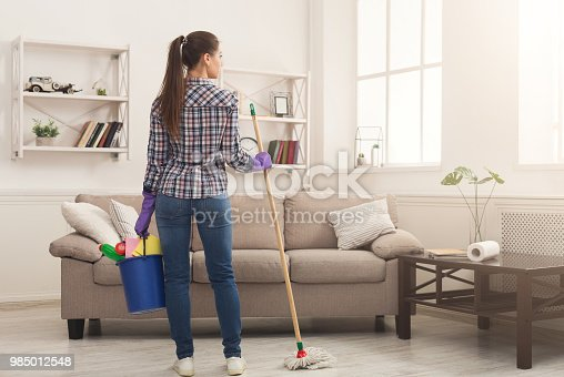 istock Woman with cleaning equipment ready to clean room 985012548