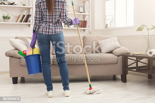 istock Woman with cleaning equipment ready to clean room 992866826