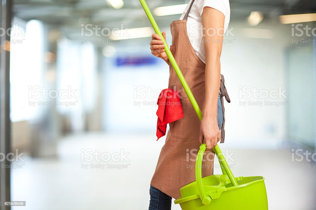 Woman with cleaning supplies in building stock photo