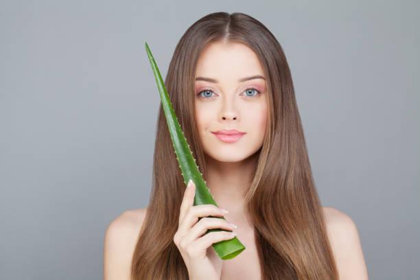 Femme avec les cheveux Long sain et clair peau tenant feuille d'aloès vert - Photo