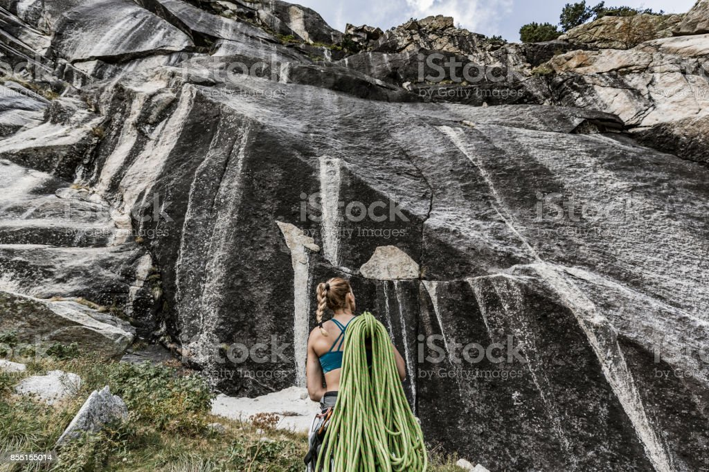 Woman with climbing equipment looking at the mountain stock photo