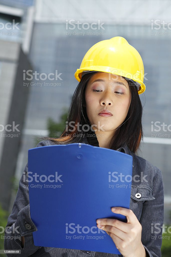 Woman with Clipboard and Hardhat stock photo
