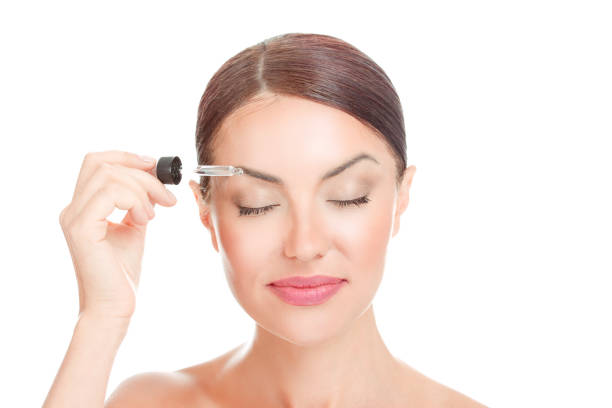 woman with closed eyes, applying serum essence essential oils to her eyebrows - serum stock photos and pictures