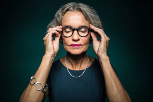 kvinna med slutna ögon hålla glasögon - mature women studio grey hair bildbanksfoton och bilder