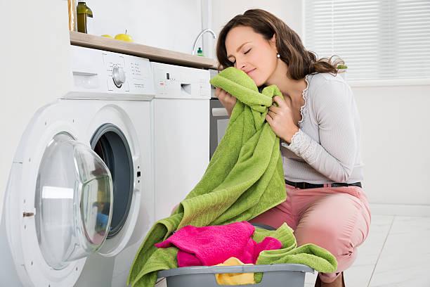 女性、衣類の洗濯機の近く - 衣類乾燥機 ストックフォトと画像