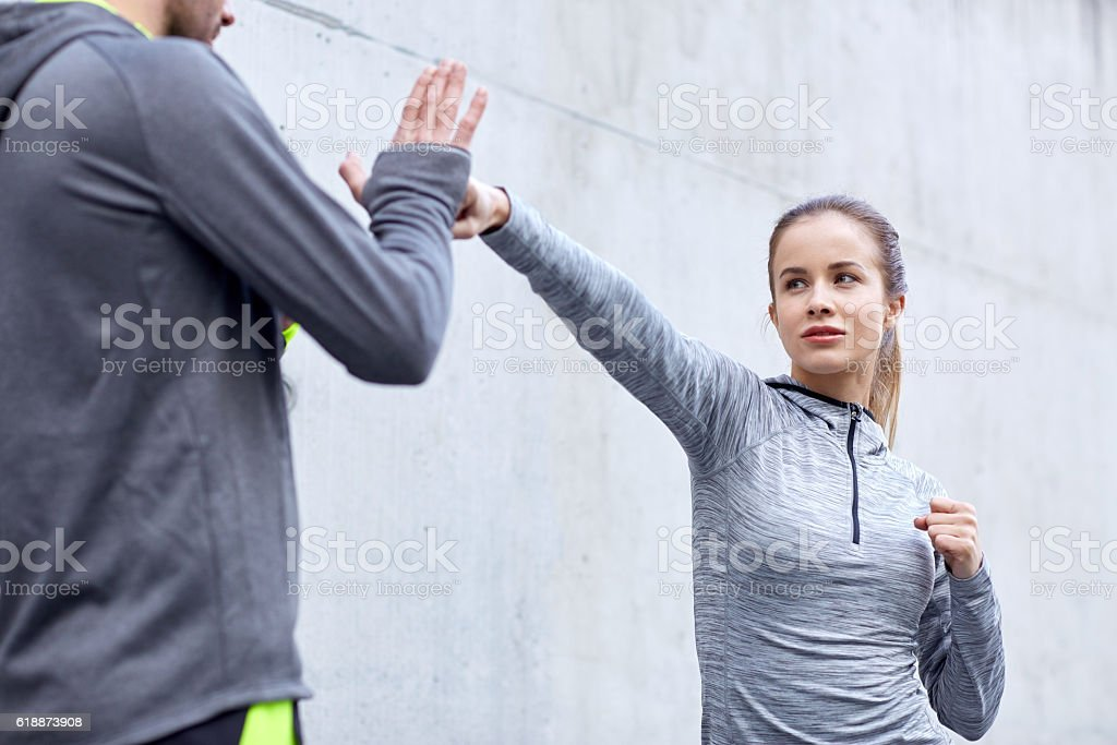woman with coach working out strike outdoors stock photo