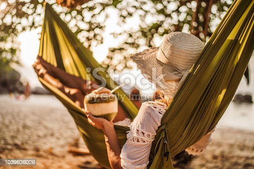 Woman relaxing in hammock at the beach while having a coconut drink.