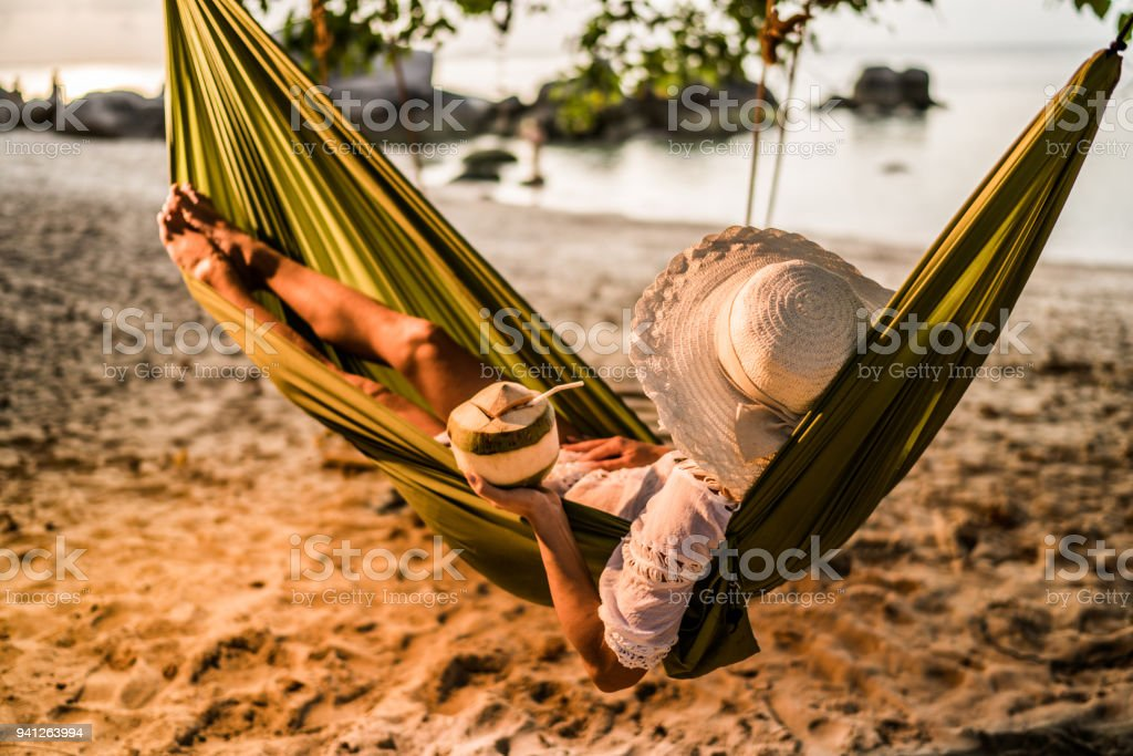 Woman with coconut drink relaxing in hammock at the beach. stock photo