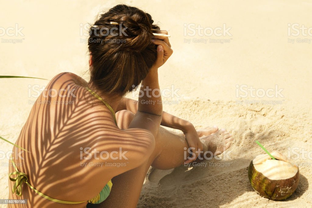 Woman with coconut drink under palm leaf Woman with coconut drink under palm leaf on the beach Adult Stock Photo