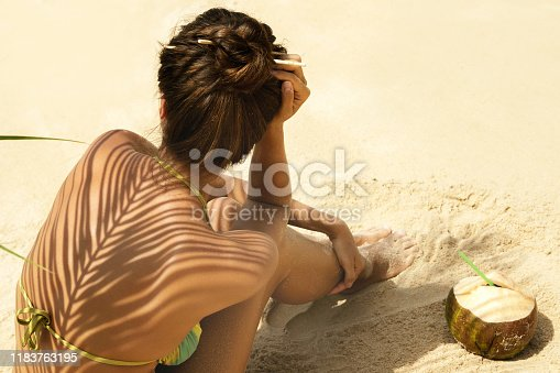Woman with coconut drink under palm leaf on the beach
