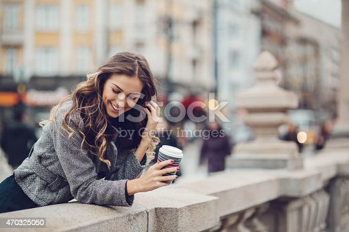 531098549 istock photo Woman with coffee cup leaning over concrete wall outside 470325050