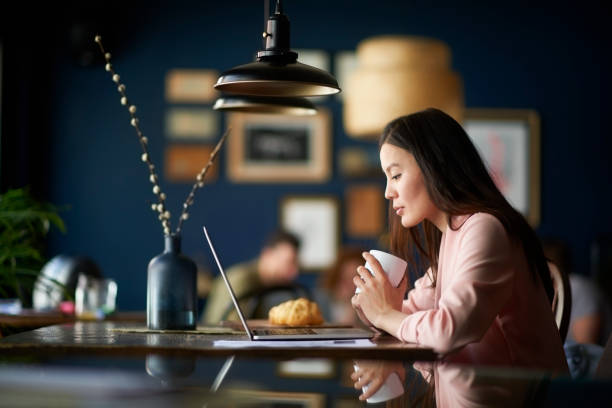 Woman with coffee cup Asian woman holding cup of coffee in cafeteria. Laptop computer, paper files and croissant are on the table. coworking stock pictures, royalty-free photos & images