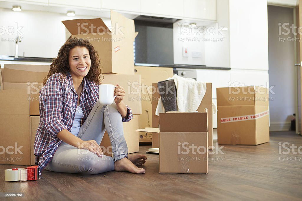 Woman with coffee cup surrounded by moving boxes stock photo