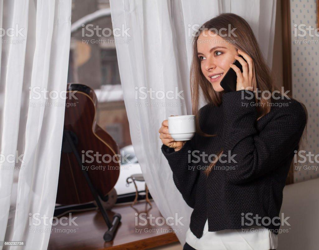 Woman with coffee near window royalty-free 스톡 사진
