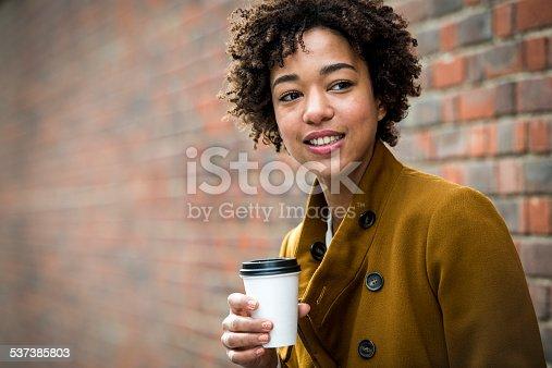 Beautiful woman enjoying coffe outdoors. Brick wall behind her.